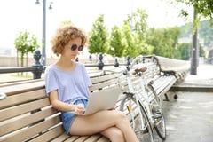 Giovane donna con il computer portatile esterno Immagine Stock