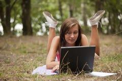 Giovane donna con il computer portatile in foresta Fotografie Stock