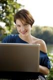Giovane donna con il computer portatile in sosta Fotografia Stock Libera da Diritti