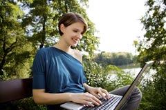 Giovane donna con il computer portatile in sosta Fotografie Stock Libere da Diritti