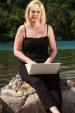 Giovane donna con il computer portatile sul lago Fotografia Stock Libera da Diritti