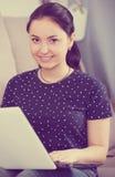 Giovane donna con il computer portatile sul sofà fotografie stock