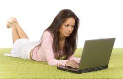 Giovane donna con il computer portatile sulla moquette verde Fotografie Stock Libere da Diritti
