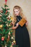 Giovane donna con il contenitore di regalo vicino all'albero del nuovo anno Fotografia Stock