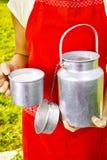 Giovane donna con il cowmilk organico fresco dell'azienda agricola in bidone di latte di alluminio Fotografie Stock Libere da Diritti