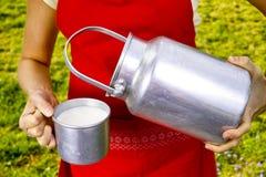 Giovane donna con il cowmilk organico fresco dell'azienda agricola in bidone di latte di alluminio Immagine Stock Libera da Diritti