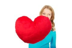 Giovane donna con il cuscino a forma di del cuore Fotografie Stock