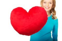 Giovane donna con il cuscino a forma di del cuore Immagine Stock Libera da Diritti
