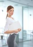 Giovane donna con il dispositivo di piegatura bianco sul lavoro Fotografia Stock