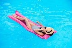 Giovane donna con il fronte della copertura del cappello di paglia che galleggia sul materasso di aria immagini stock libere da diritti