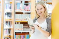 Giovane donna con il libro in biblioteca Fotografie Stock