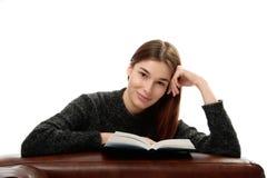 Giovane donna con il libro che si appoggia mobilia di cuoio Fotografie Stock Libere da Diritti