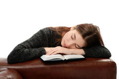 Giovane donna con il libro che si appoggia mobilia di cuoio Immagine Stock