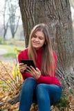 Giovane donna con il libro elettronico nel parco di autunno Immagini Stock Libere da Diritti