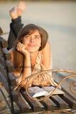 Giovane donna con il libro su un banco Fotografie Stock