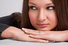 Giovane donna con il mento sulle mani che osservano obliquamente immagini stock libere da diritti