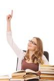 Giovane donna con il mucchio dei libri che indica su Fotografia Stock