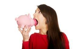 Giovane donna con il porcellino salvadanaio in bocca Fotografie Stock