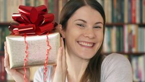 Giovane donna con il presente Contenitore di regalo dorato della tenuta femminile con il nastro rosso che celebra compleanno stock footage