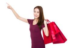 Giovane donna con il punto del dito alto e tenuta con il sacchetto della spesa Fotografie Stock Libere da Diritti