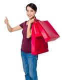 Giovane donna con il sacchetto della spesa ed il pollice su Fotografia Stock