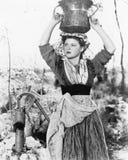 Giovane donna con il secchio di acqua sulla sua testa accanto ad un pozzo (tutte le persone rappresentate non sono vivente più lu Fotografie Stock