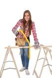 Giovane donna con il seghetto a mano per metalli giallo Fotografia Stock