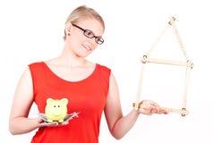 Giovane donna con il simbolo della casa e la banca piggy Fotografia Stock Libera da Diritti