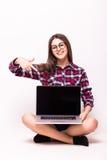 Giovane donna con il sorriso felice amichevole che tiene un computer portatile e che indica allo schermo Immagini Stock