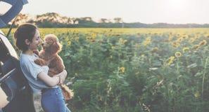 Giovane donna con il suo cane che sta vicino all'automobile Immagine Stock