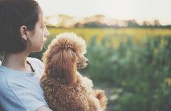 Giovane donna con il suo cane che sta vicino all'automobile Fotografia Stock