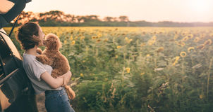Giovane donna con il suo cane che sta vicino all'automobile Immagini Stock