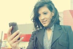 Giovane donna con il telefono cellulare che cammina, costruzione blured di affari dentro immagini stock libere da diritti