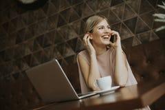 Giovane donna con il telefono cellulare ed il computer portatile alla tavola in caffè Fotografie Stock