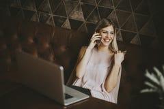 Giovane donna con il telefono cellulare ed il computer portatile alla tavola in caffè Fotografia Stock Libera da Diritti