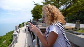 Giovane donna con il telefono cellulare vicino al mare video d archivio