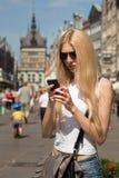 Giovane donna con il telefono in mani sulla via Immagine Stock
