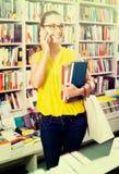 Giovane donna con il telefono nel negozio di libro Immagine Stock