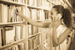 Giovane donna con il telefono nel negozio di libro Fotografia Stock