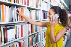 Giovane donna con il telefono nel negozio di libro Fotografia Stock Libera da Diritti