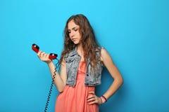 Giovane donna con il telefono rosso fotografia stock