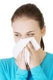 Giovane donna con il tessuto - starnutendo. Allergia o freddo. Immagine Stock