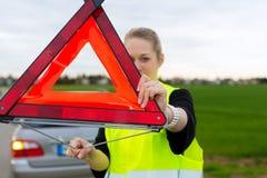Giovane donna con il triangolo d'avvertimento sulla via Fotografie Stock Libere da Diritti