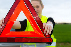 Giovane donna con il triangolo d'avvertimento sulla via Immagine Stock