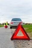 Giovane donna con il triangolo d'avvertimento sulla via Immagine Stock Libera da Diritti