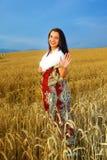 Giovane donna con il vestito ornamentale e la pelliccia bianca Fotografia Stock