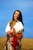 Giovane donna con il vestito ornamentale e la pelliccia bianca Fotografia Stock Libera da Diritti