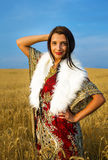 Giovane donna con il vestito ornamentale e la pelliccia bianca Fotografie Stock
