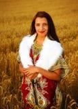 Giovane donna con il vestito ornamentale e la pelliccia bianca Immagine Stock Libera da Diritti