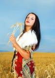 Giovane donna con il vestito ornamentale e la pelliccia bianca Immagini Stock